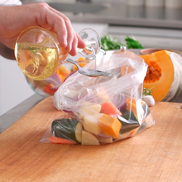 Measuring table spoon of oil over cut vegetable in plastic bag