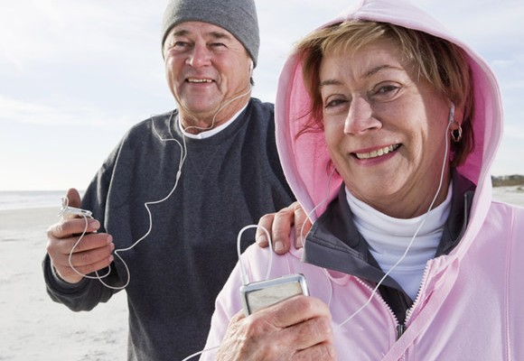 Mature couple exercising with earphones and device playing