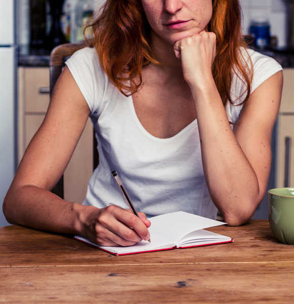 Woman sitting at table writing