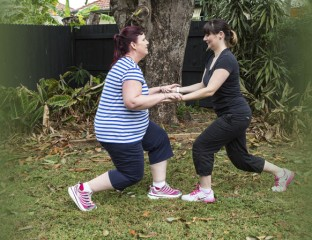 Two women doing single leg squats holding hands