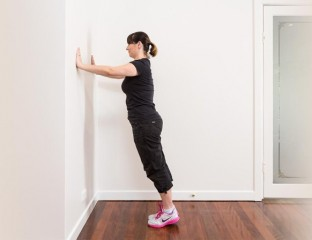 Woman doing pushups against wall